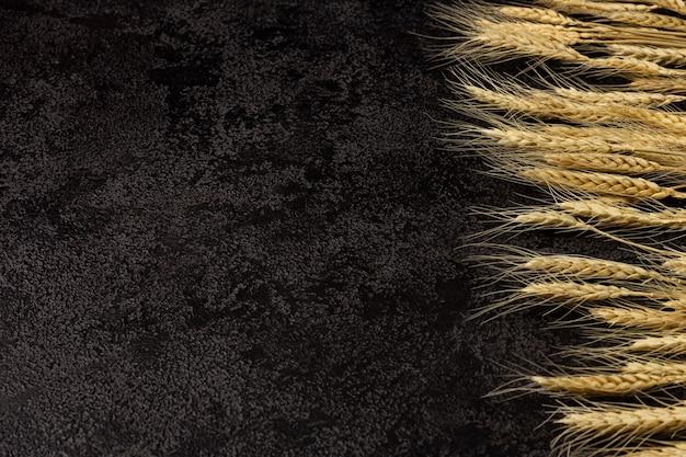 Sackleinen serviette auf einem dunklen strukturellen hintergrund draufsicht weizenähren copyspace draufsicht