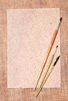 Sackleinen und papier mit bürstenhintergrundschablone mit platz für text oder zeichnung