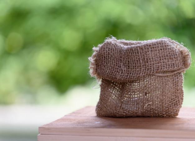 Sackleinenbeutel auf holztischplatte mit naturgrünem hintergrund, platz für produkte