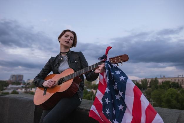 Sänger mit der us-flagge, die gitarre auf bewölktem himmelshintergrund spielt. akustikkonzert auf dem dach. ein teenager im urlaub auf einer party am unabhängigkeitstag