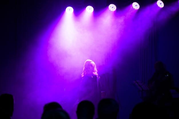 Sänger mit mikrofon auf der bühne in bühnenbeleuchtung.
