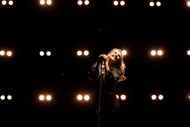 Sänger singt zum mikrofon. sänger in der silhouette