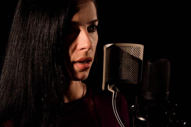 Sängerin der jungen frau vor mikrofon.