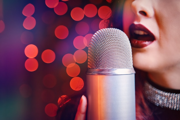 Sängerin mit disco-mikrofon auf hellem bokeh-hintergrund nahaufnahme von frauenlippen mit burgunder bemalt ...