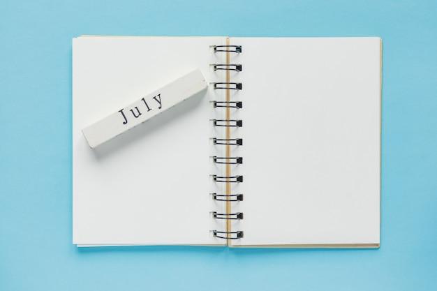 Säubern sie gewundenes anmerkungsbuch für anmerkungen und mitteilungen und hölzerne kalenderleiste des julis