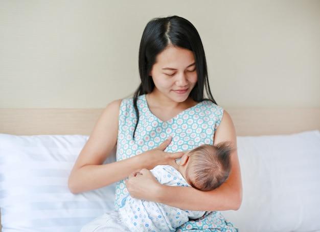 Säuglingsbaby, das von der mutter stillt ihr neugeborenes kind auf dem bett einzieht.