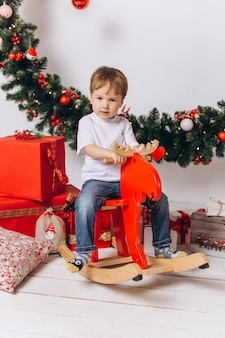 Säuglingsbaby, das zu hause am weihnachtsabend spielt. feiertagsdekorationen, silvester mit bunten lichtern sind auf hintergrund