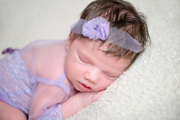 Säuglingsbaby im spitzenviolett-outfit