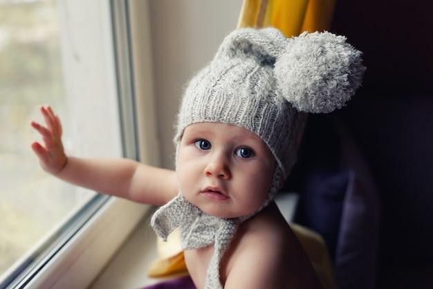 Säuglingsbaby in strickmütze sitzt auf der fensterbank und berührt glas, will laufen, gefahr