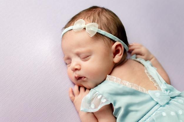 Säuglingsbaby schläft süß in einem schönen kleid