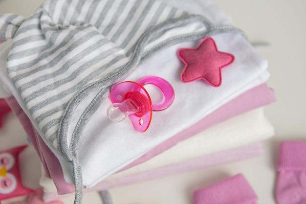 Säuglingsbabykleidung baby schnullerkappe auf hintergrund