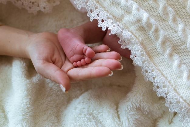 Säuglingsfüße in weißen kleidern