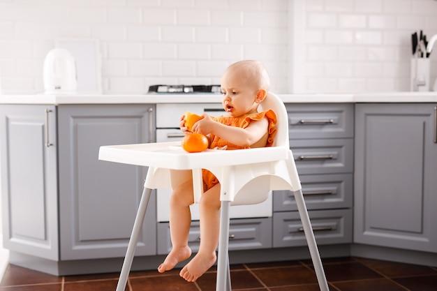 Säuglingsmädchen, das im hohen kinderstuhl sitzt und früchte auf weiß isst