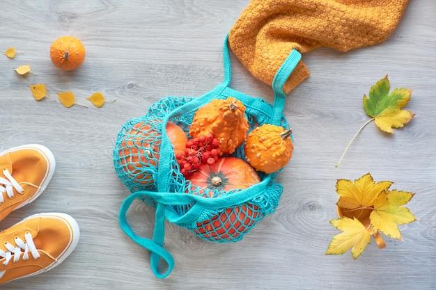 Safran gelbe und orange kürbisse in netzbeutel oder netzbeutel von weiblichen händen in gelbem pullover geöffnet. herbstwohnung lag auf hellem holz