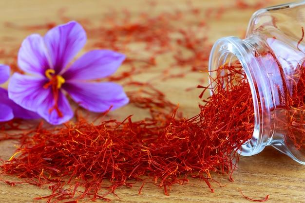 Safran narben auf einer holzoberfläche aus einer glasflasche verstreut. safrankrokusblüten. blühender safransativus.