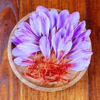 Safranblüten und staubblätter in einem holzteller. rote staubblätter von safran sativus, aus denen das teuerste gewürz hergestellt wird.