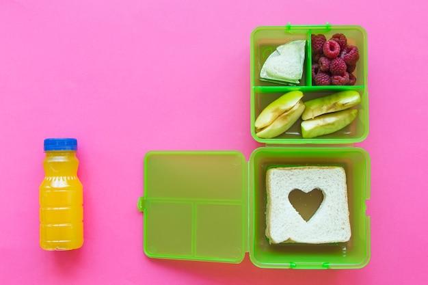 Saft in der nähe von lunchbox mit essen