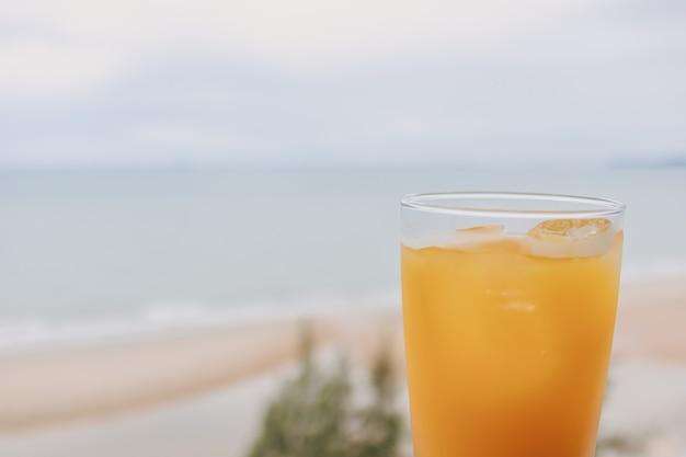 Saft in einem glas mit meerblickhintergrund im konzept des sommers