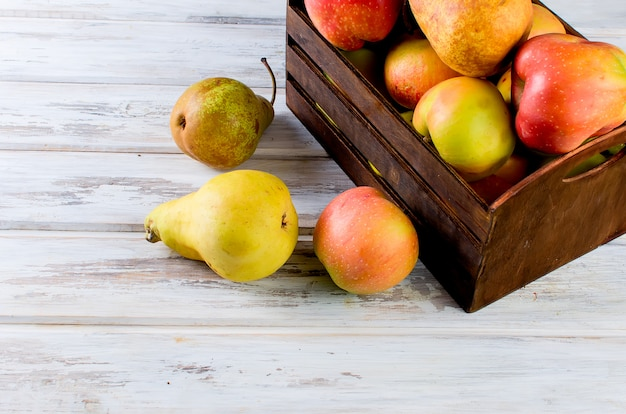 Saft in einem glas und reifen äpfeln und birnen auf einem holztisch
