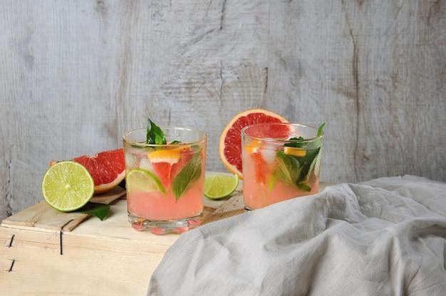 Saftcocktail gepresste rote grapefruit und blätter von zarten zitronen-basilikum-limettenscheiben und gekühlten eiswürfeln