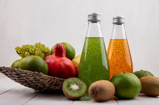 Saftflaschen der vorderansicht mit granatäpfeltrauben-mandarinen und birnen in einem korb auf einer weißen wand