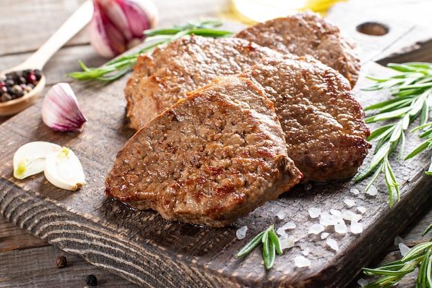 Saftig dicke saftige portionen gebratenes steakfilet mit gewürzen auf einem alten holzbrett