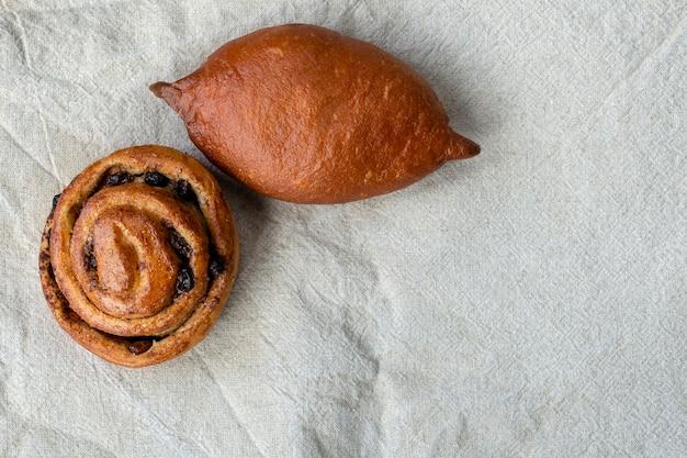 Saftig gebackene torte und brötchen mit zimt und rosinen auf einer leinenserviette