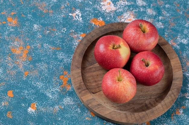 Saftige äpfel auf runder holzplatte.