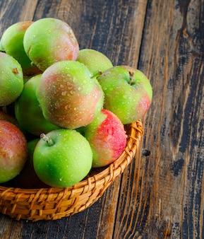 Saftige äpfel in einem weidenkorb auf einem hölzernen hintergrund. nahansicht.