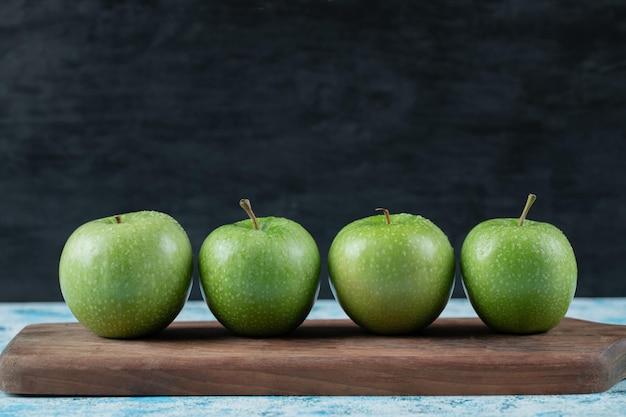 Saftige äpfel in reihe auf holzbrett.