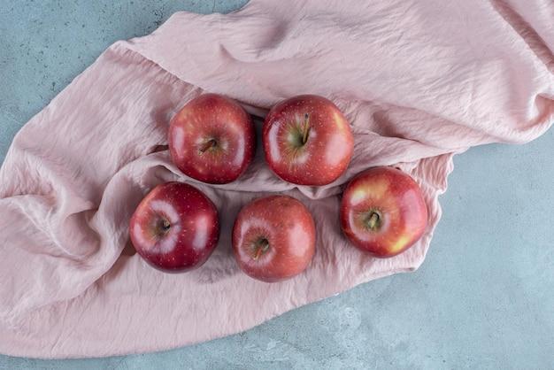 Saftige äpfel isoliert auf einer rosa tischdecke.