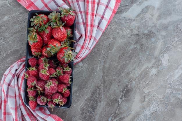 Saftige beerenplatte mit erdbeeren und himbeeren auf marmor.