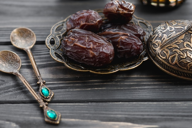 Saftige datteln auf metallischer platte mit türkischen mustern und verzierungslöffeln auf tabelle