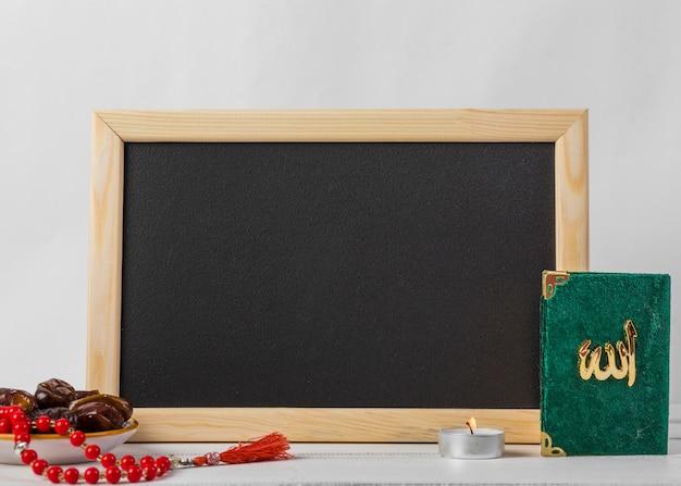 Saftige datteln; rote rosenkranzperlen; kerze und heiliges kuran buch vor schwarzer tafel vor weißem hintergrund