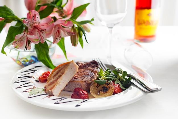 Saftige dicke saftige portionen vom gegrillten filetsteak mit tomaten und gebratenem gemüse