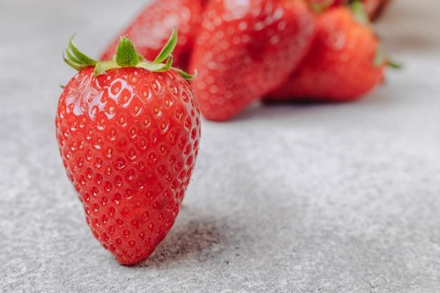 Saftige erdbeeren auf einem konkreten hintergrund