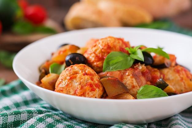 Saftige fleischbällchen aus putenfleisch mit gemüse (zucchini, auberginen, oliven, tomaten)
