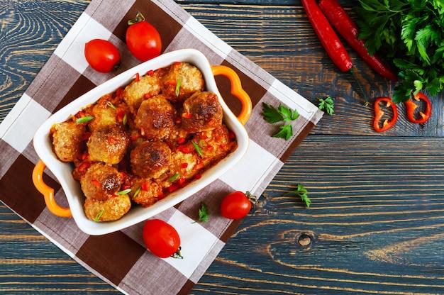Saftige fleischbällchen in einer würzigen tomatensauce auf einem holztisch. gericht aus hackfleisch. die draufsicht
