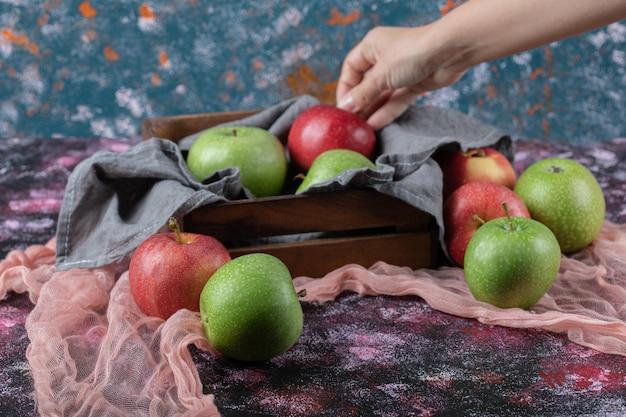 Saftige frische äpfel auf rustikalem holztablett.