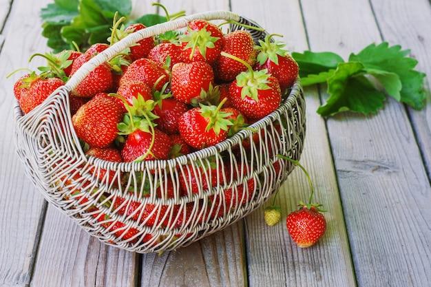 Saftige frische erdbeeren in einem korb auf weißem hölzernem, selektivem fokus