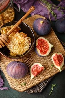 Saftige frische ganze feigenfrüchte und eine geschnittene feige und eine schüssel honig in waben auf holzschneidebrett. draufsicht