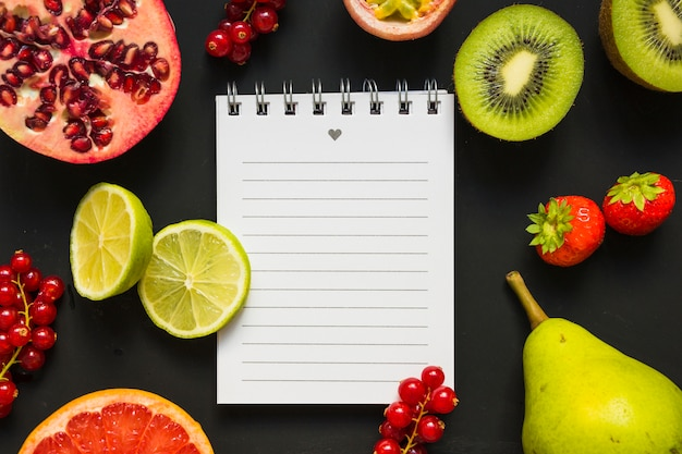Saftige gesunde früchte mit gewundenem notizblock auf schwarzem hintergrund