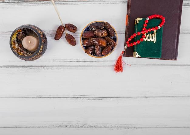 Saftige getrocknete dattelschüssel; kerze; tagebuch; kuran und islamische rosenkranzgebetsperlen auf weißem hölzernem schreibtisch