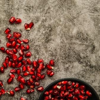 Saftige granatapfelsamen in der schüssel und auf beflecktem hintergrund