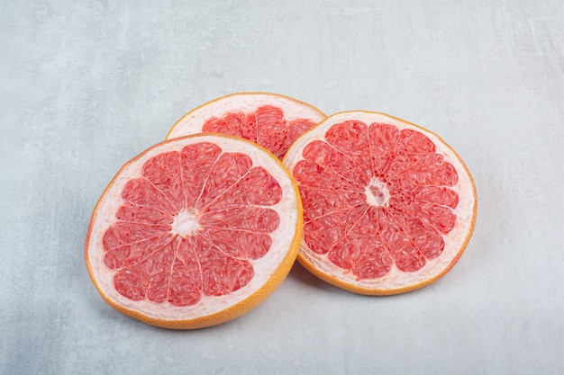 Saftige grapefruitscheiben auf steinhintergrund