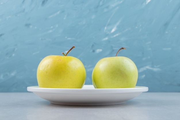Saftige grüne äpfel auf weißem teller