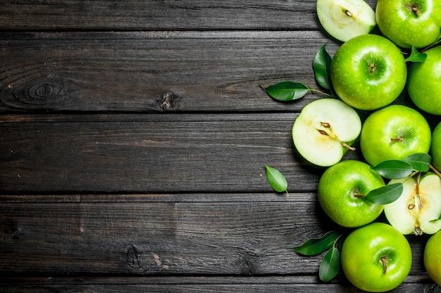 Saftige grüne äpfel mit blättern. auf hölzernem hintergrund.