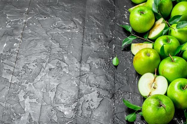 Saftige grüne äpfel mit blättern und apfelscheiben. auf einem dunklen rustikalen hintergrund.