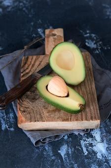 Saftige grüne avocado geschnitten mit einem knochen auf einem rauen dunklen hintergrund