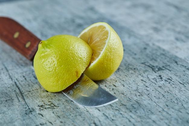 Saftige halb geschnittene gelbe zitrone auf marmoroberfläche mit messer